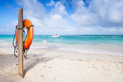 Red round life buoy hanging on wooden pole Stock Image