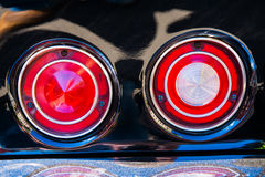 Red round rear lights of a black sport car. Color and beauty of vintage cars. Red round rear lights of a black sport car. Chrome plated bumper is covered with a Stock Image