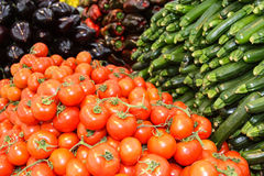 Red round tomatoes, zucchini and peppers. Grocery Store. Many tomatoes and cucumbers on display in a groceries supermarket Stock Images