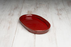 Red Rounded Rectangular Shallow Dish on White Wooden Panel Surfa Royalty Free Stock Photography