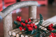 Red rowan on a wooden bench. Red winter snow-covered mountain ash on a wooden bench Stock Image