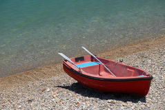 Red rowboat  on beach. Red boat at the mediterranean sea in Greece near Corinth Stock Image