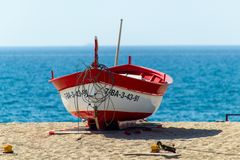 Red rowboat on the sand near the sea royalty free stock photo