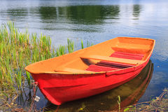 Red rowing boat. On lake royalty free stock photography