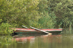 Red rowing boat on lake Stock Images