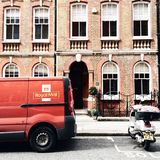 Red Royal Mail Parked Near Brown Brick Building Stock Photo