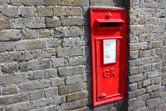 Red Royal Mail post box in brick wall Stock Photo