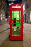 Red royal telephone booth in London city night scene. Sidewalk evening stroll Royalty Free Stock Images