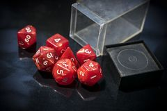Red RPG dice. A container with spilled red RPG dice on a black table royalty free stock image