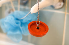Red rubber bath plug on chain Stock Photo