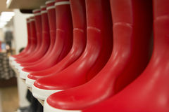 Red rubber boots of different colors on store shelves Stock Photo