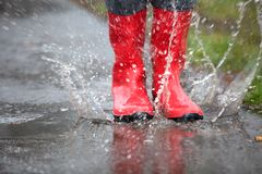 Red rubber boots are jumping into a big puddle. A pair of red rubber boots are jumping into a big puddle Stock Photos