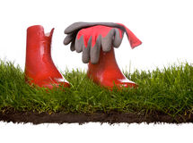 Red Rubber Garden Boots. Grass lawn with red rubber gardening boots and gloves Royalty Free Stock Photography