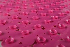 Red rubber mat for bath with pattern as background, inverse. Red rubber mat for bath with pattern as background. Red inverse rubber mat with suction cups and stock images