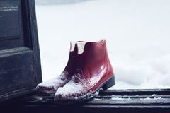 Red rubber shoes covered in snow by the door. Front view of a pair of red  rubber shoes by the house wooden open door entrance covered in snow in winter time Stock Photo
