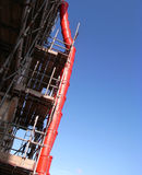 Red rubbish chute and blue sky. A red plastic waste chute and scaffolded building against blue sky Stock Image