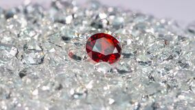 Red ruby diamonds are placed on a pile of white diamonds