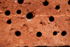 Red rugged brick with holes Royalty Free Stock Images