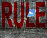 Red RULE word on grey grunge concrete wall Royalty Free Stock Image