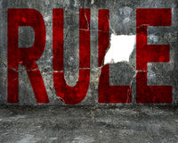 Red rule word on mottled concrete wall with large hole Stock Photos