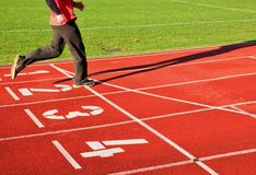 Red running racetrack on the stadium with two running legs in tracksuit trousers Royalty Free Stock Image