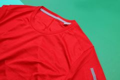 Red running shirt on green background Stock Photos