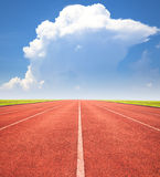 Red running track over blue sky and clouds Stock Photography