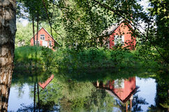Red rural home reflected through branches on pond Stock Photos