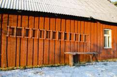 Red rural wooden house wall in winter with ladder royalty free stock image