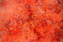 Red rust color facade stone wall with imperfections, holes and cracks as an empty rustic and simple abstract texture surface backg royalty free stock images