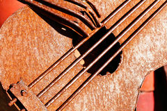 Red Rusted Metal Bass Guitar with hand. A red rusty metal likeness of a bass guitar with strings, and hand with fingers Royalty Free Stock Images