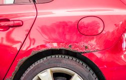 Red rusted and scratched car with damaged rusty paint in crash accident or parking lot. And dented damage of metal body from collision stock image