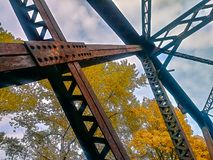 Red rusted steel beams fall. Rust colored beams against fall trees and sky Royalty Free Stock Image