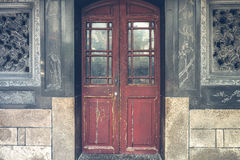 Red rustic door on black antique wall Royalty Free Stock Photo