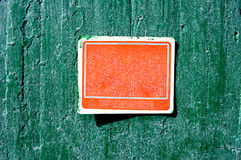 Red rusty grungy old plastic sign on a cement wall Stock Image