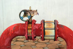 Red rusty metal industrial water pipes with a valve. Royalty Free Stock Images