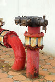 Red rusty metal industrial water pipes with a valve. Royalty Free Stock Image