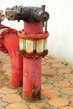 Red rusty metal industrial water pipes with a valve. Stock Image