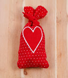Red sachet bag with a heart on wooden background. Red sachet bag with white heart on wooden background Stock Photo