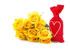 Red sachet bag with a heart and yellow roses. Isolated over white Stock Photos