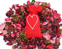 Red sachet with a heart in the background of petals. Over white Royalty Free Stock Images