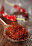 Red saffron. On wooden spoon closeup Royalty Free Stock Photo