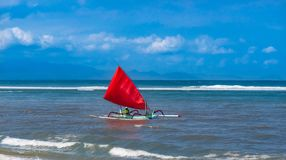 Red sail on a colorful traditional Balinese boat. Red sail on a colorful wooden traditional Balinese boat royalty free stock photography