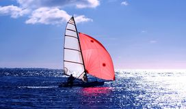 Red sail dinghy. A lone sailor sails a dinghy with a red sail royalty free stock images