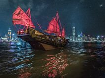 Red Sail Junk Boat on Victoria Harbour in Hong Kong. A red sailed junk boat sails in front of the neon covered buildings on the Victoria Harbour light show in royalty free stock photo
