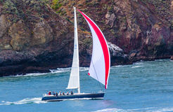 Red Sail. San Francisco, CA, USA - May 21, 2016: A blue sailboat with a red and white sail cruising in San Francisco royalty free stock photos