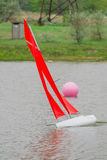 Red sail yacht. Red sail remote controlled model of yacht altering course to starboard near a pink buoy Royalty Free Stock Images