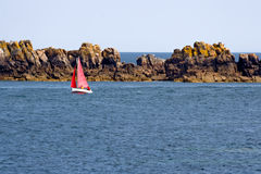 Red sailboat in the Atlantic Ocean. Coast Stock Photo