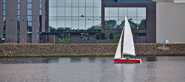 Red sailboat in front of a waterfront building stock image