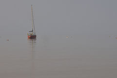 A red sailboat sits in a cove in fog Stock Photos